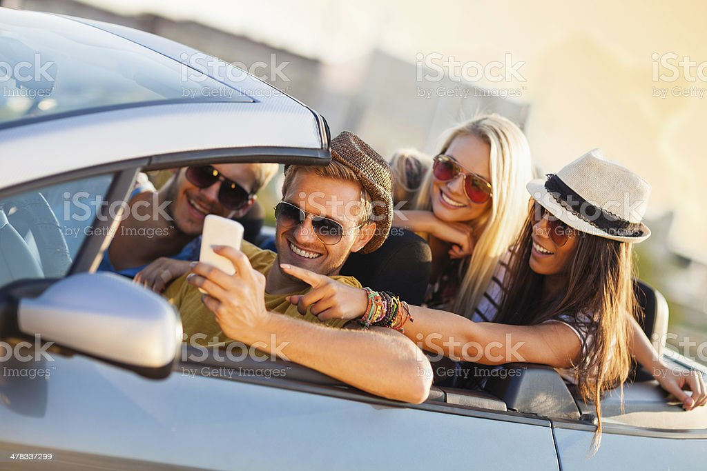 Happy young people looking at mobile phone royalty-free stock photo
