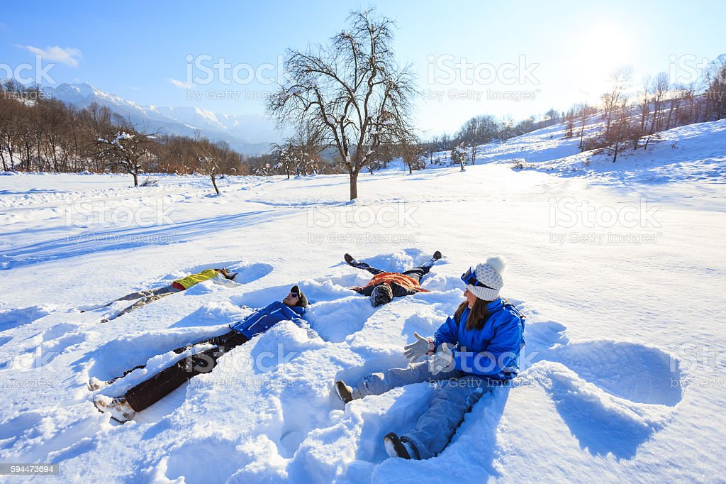 Happy young people making snow angels stock photo