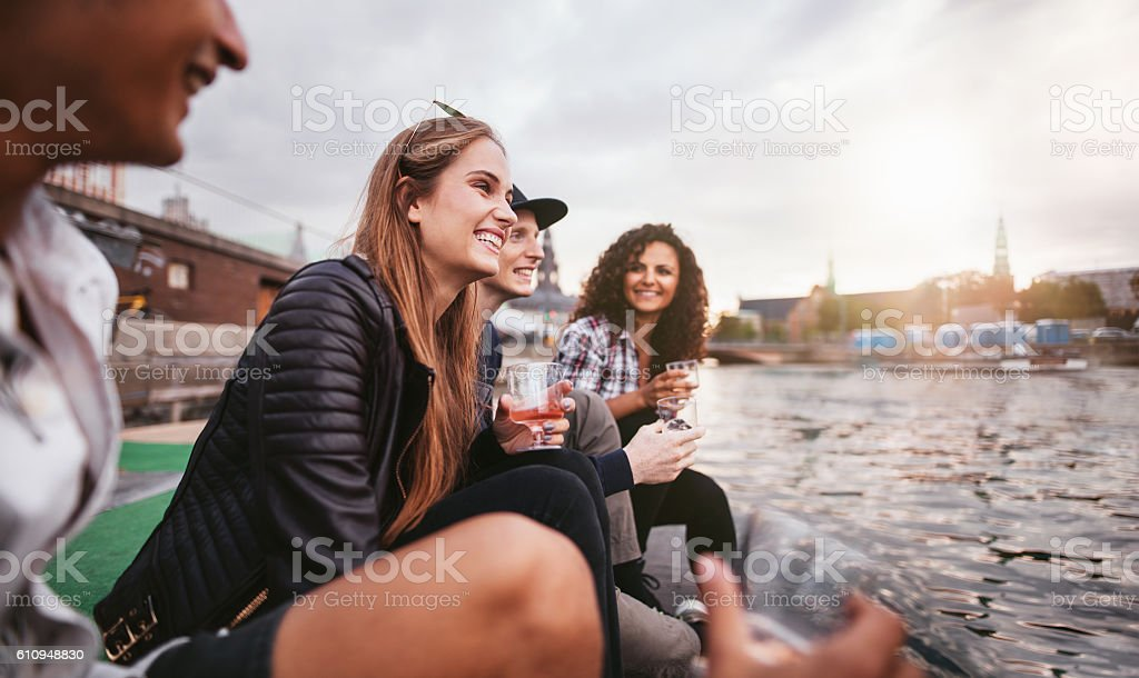 Happy young people relaxing by the lake stock photo