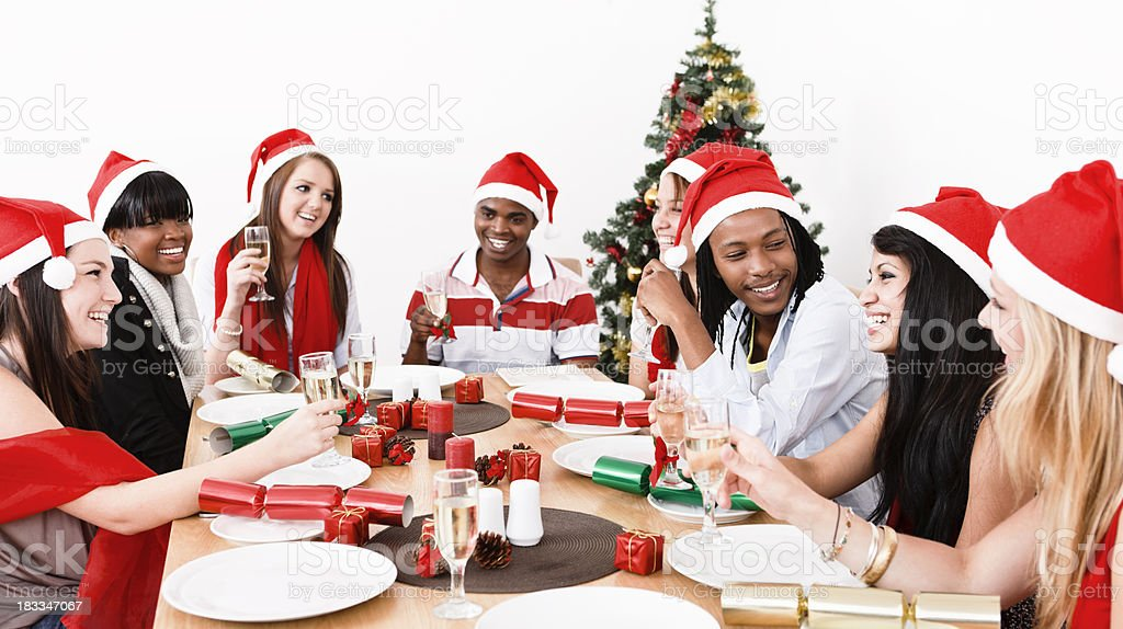 Happy young people round Christmas dinner table royalty-free stock photo
