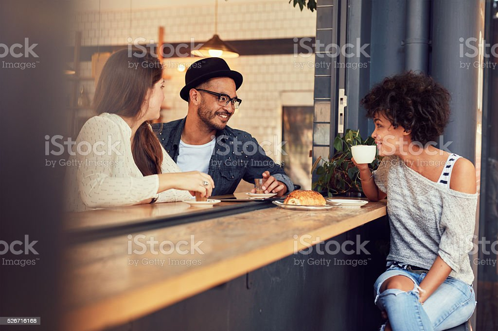 Happy young people sitting in a cafe stock photo