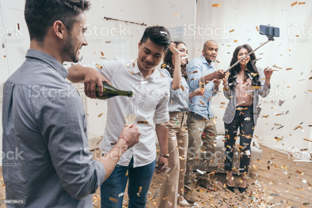 Happy young people taking selfie while celebrating with champagne and confetti stock photo