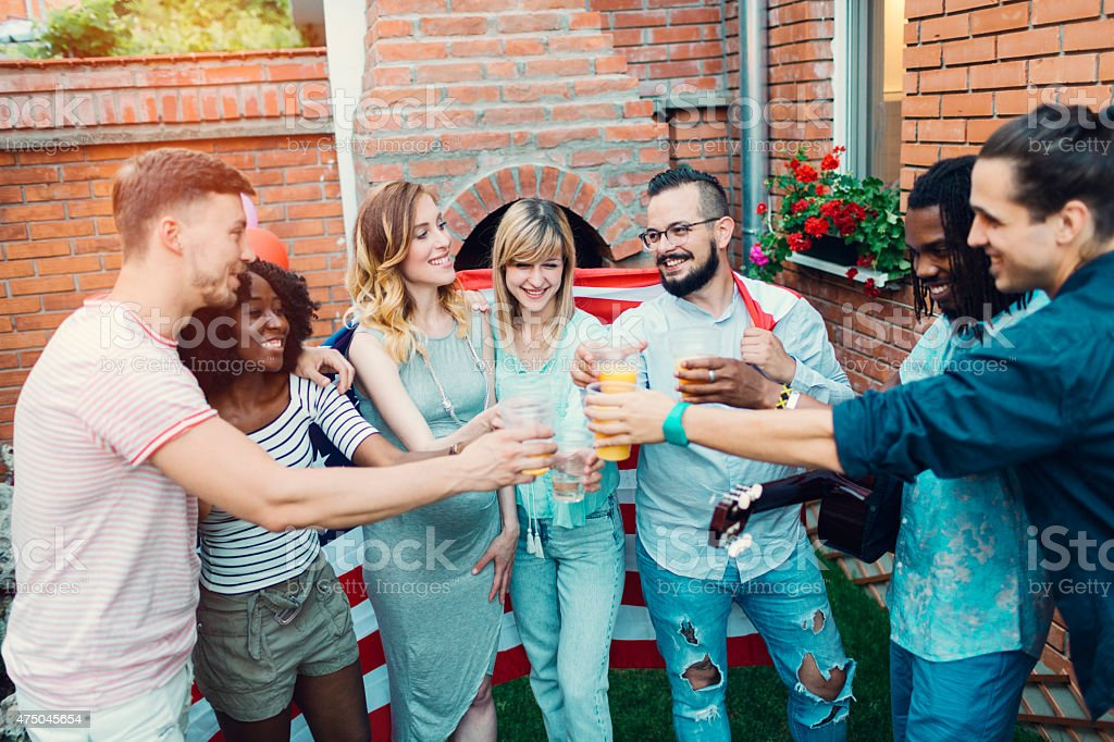 Happy Young People Toasting At Backyard Party. stock photo
