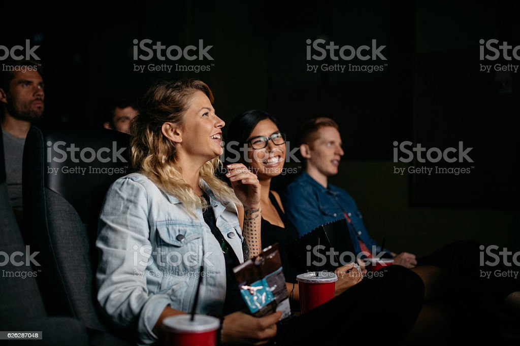 Happy young people watching movie in cinema stock photo