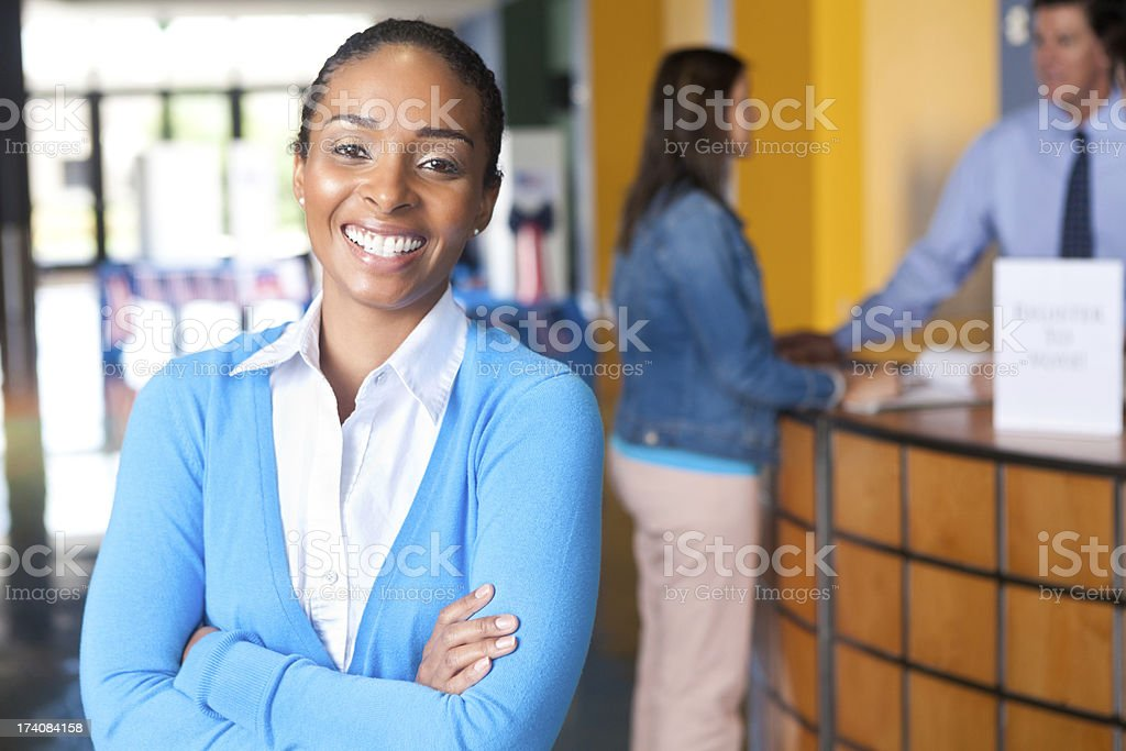 Happy young professional woman smiling at a voting center stock photo