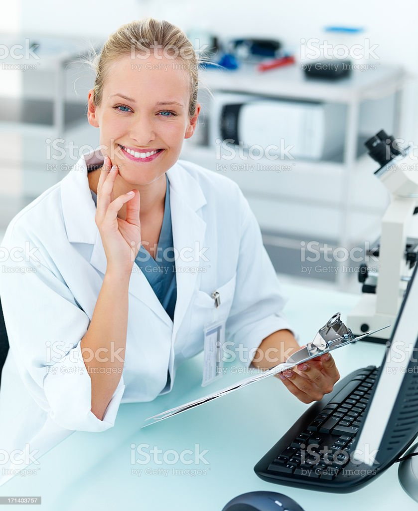 Happy young researcher by microscope smiling royalty-free stock photo