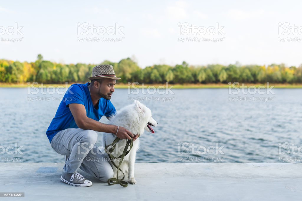 Happy young sri lankan man with her dog white samoyed sitting by the river. stock photo