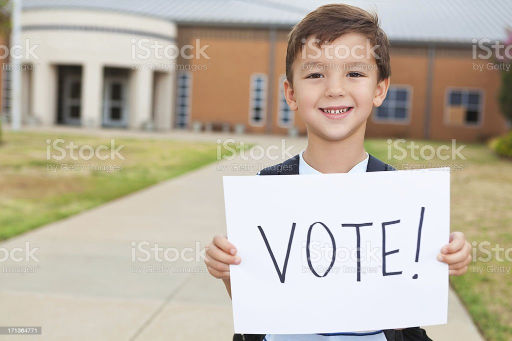 Happy young student at school holding a Vote Sign stock photo