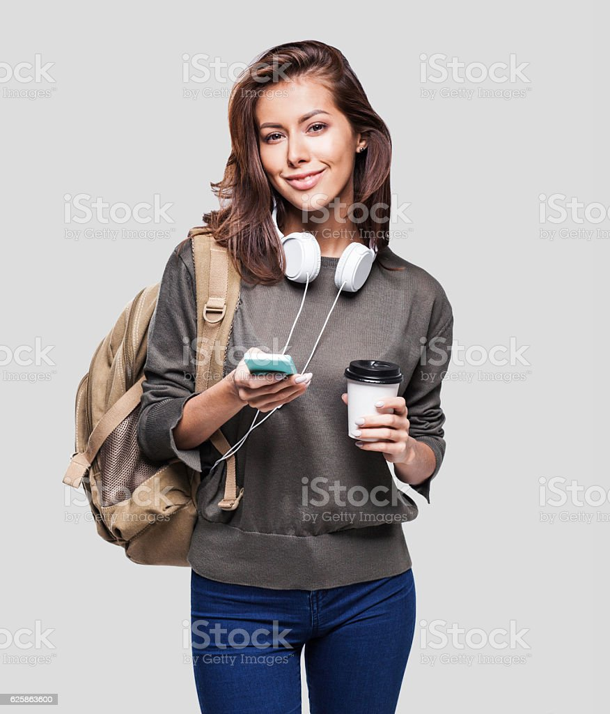 Happy young student girl using smart phone stock photo