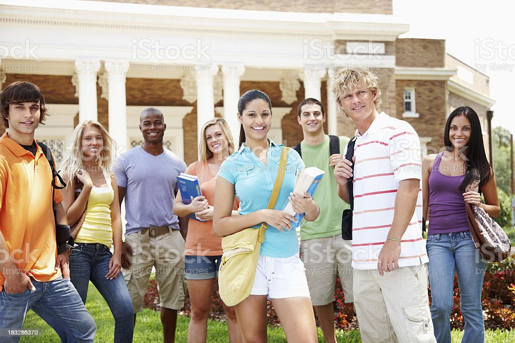 Happy young students standing outside the university building royalty-free stock photo