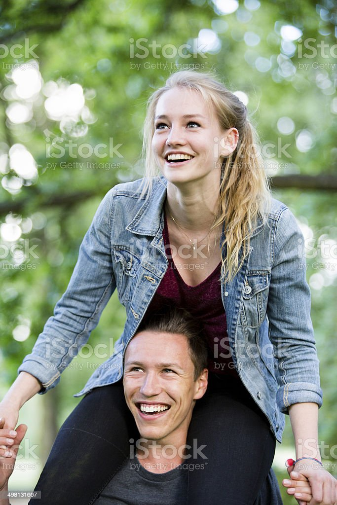happy young teenage couple having fun with piggyback royalty-free stock photo