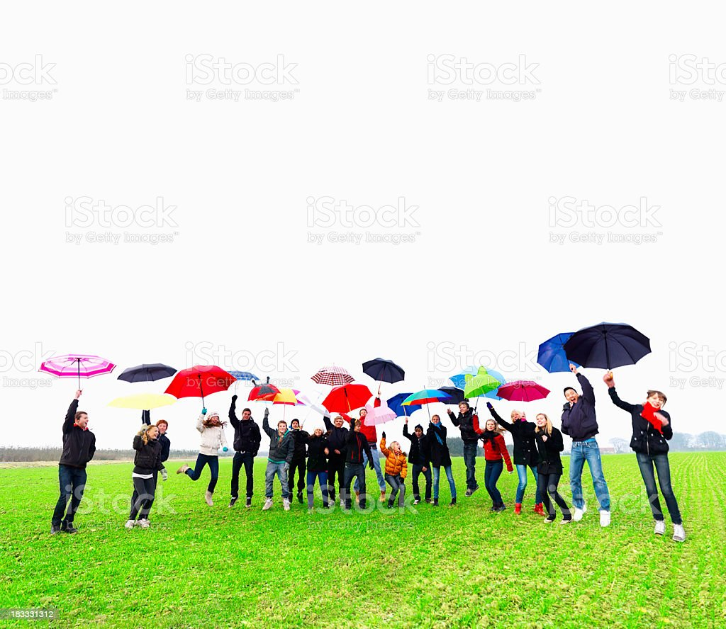 Happy young teens jumping while holding umbrellas royalty-free stock photo