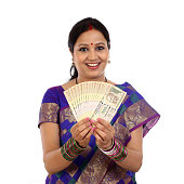 Happy young traditional woman holding Indian currency