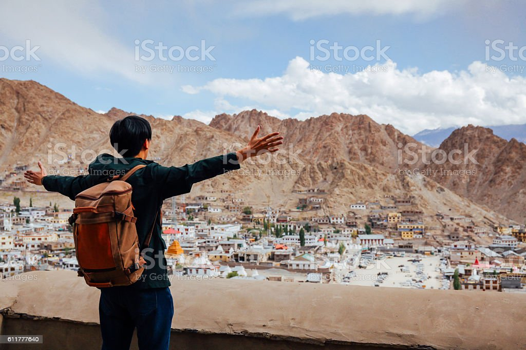 Happy young traveler spreading arms in old city background stock photo