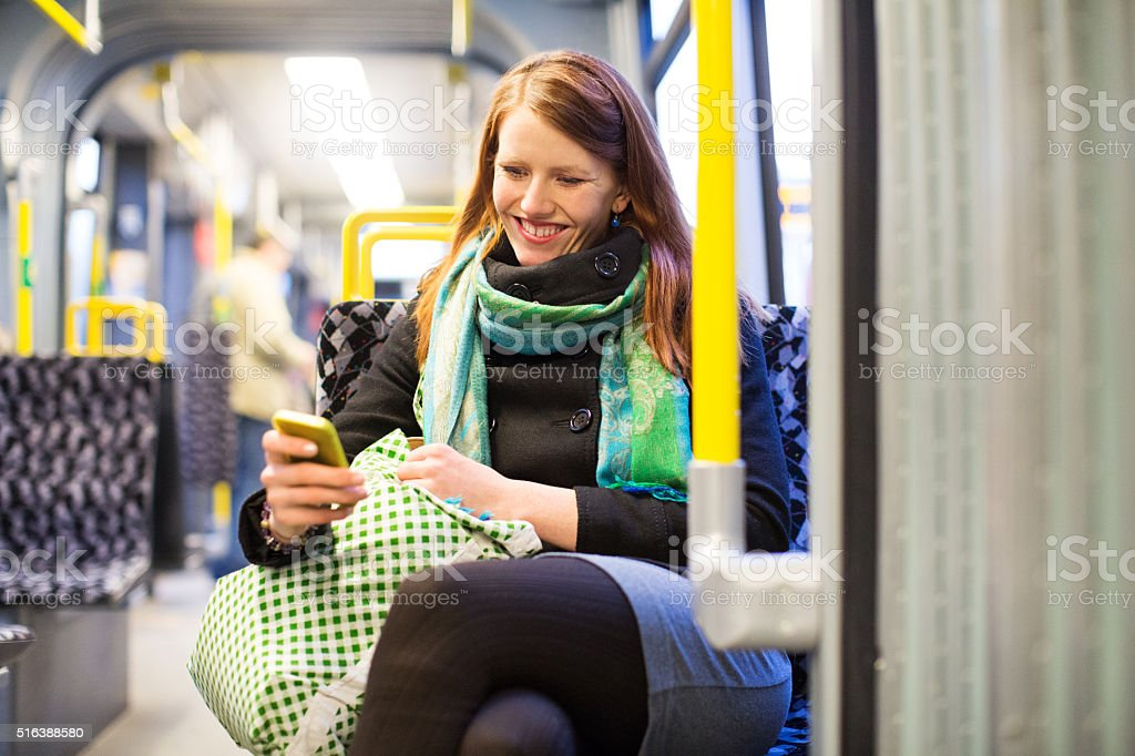 Happy young traveling by subway train using mobile phone stock photo