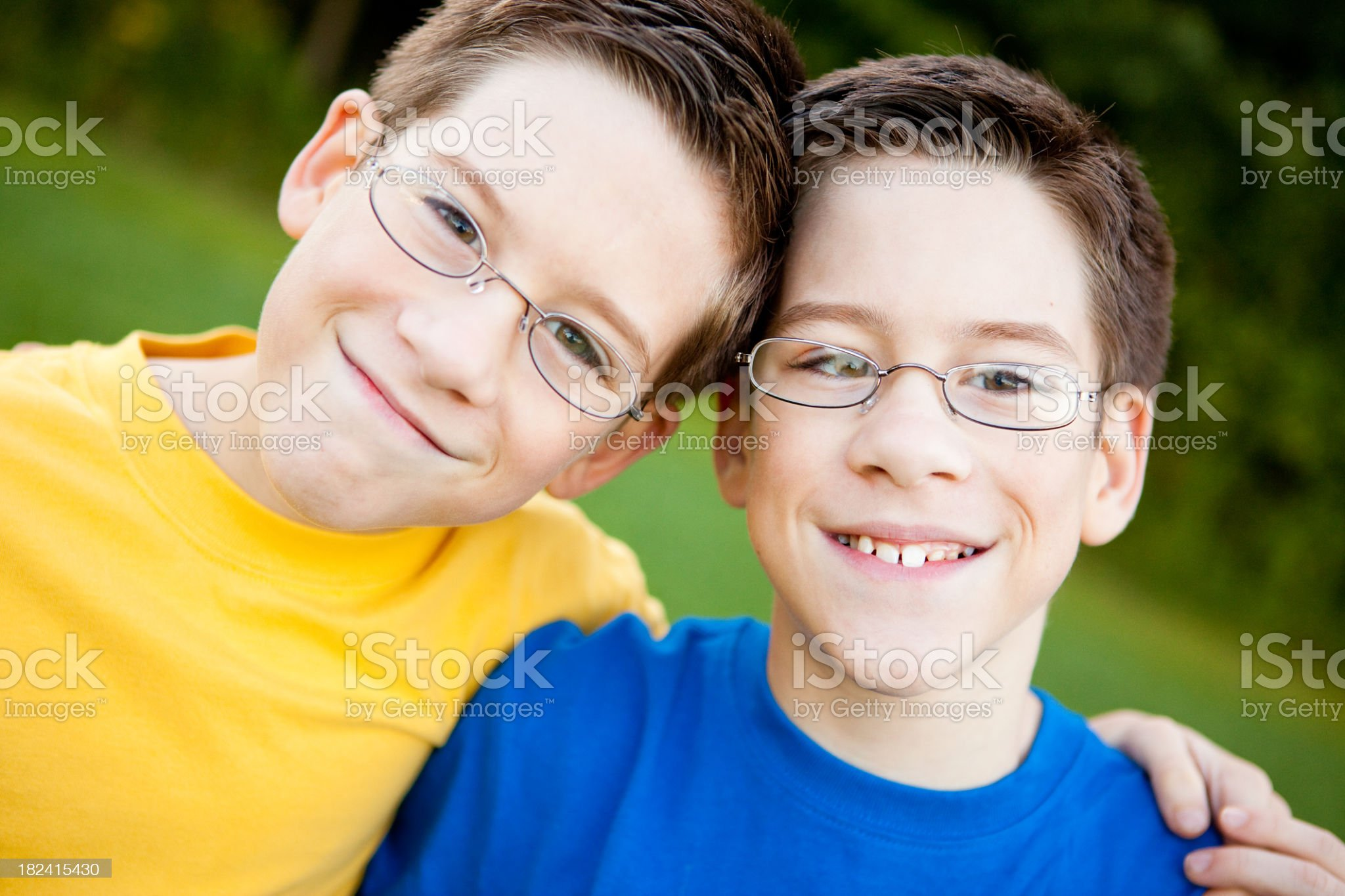 Happy Young Twin Boys with Glasses Smiling Outside royalty-free stock photo
