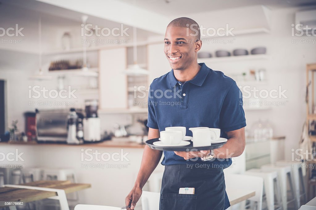 Happy young waiter with coffee cups on tray stock photo