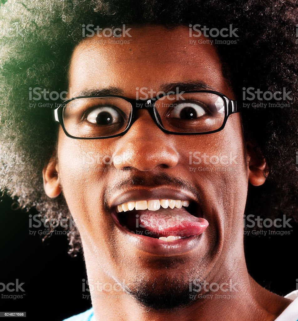 Happy young wide-eyed geek plays the fool, sticking tongue out stock photo