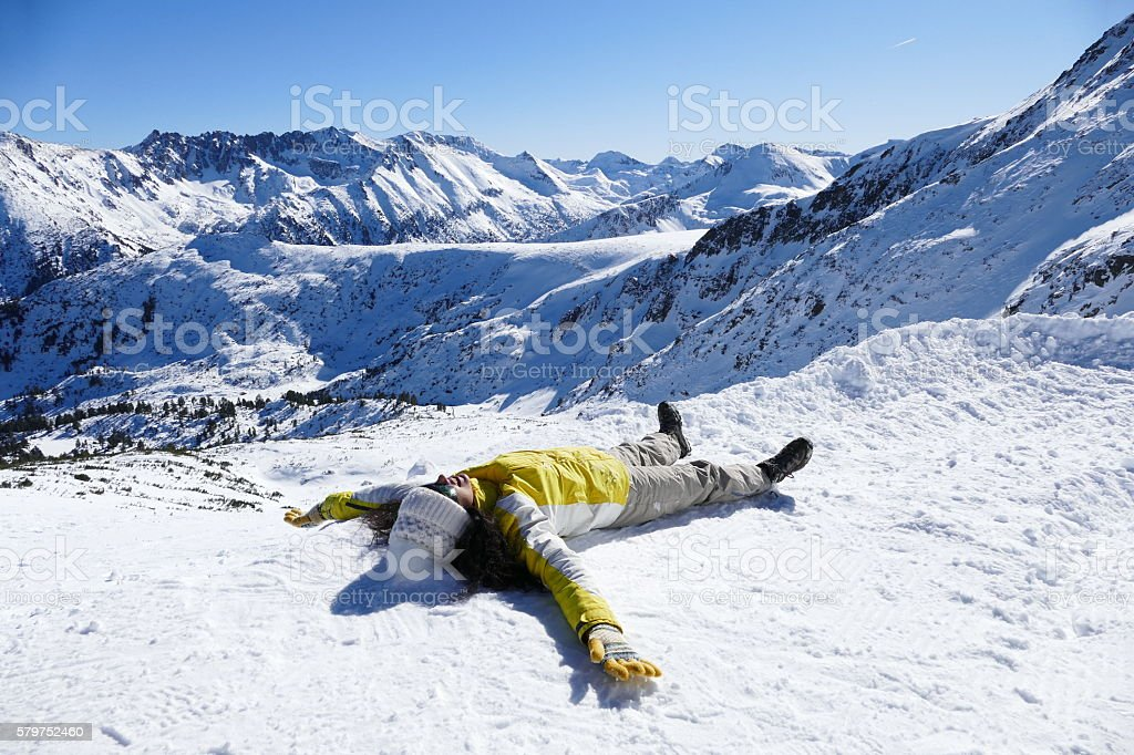 Happy young woamn making snow angel stock photo