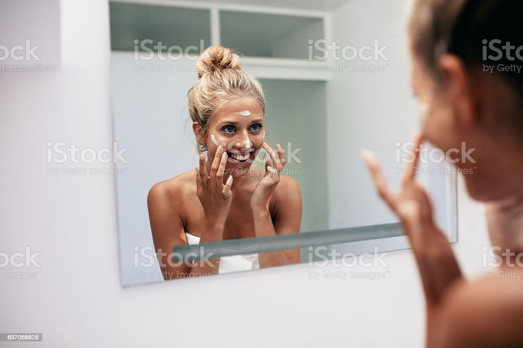Happy young woman applying cream in bathroom stock photo