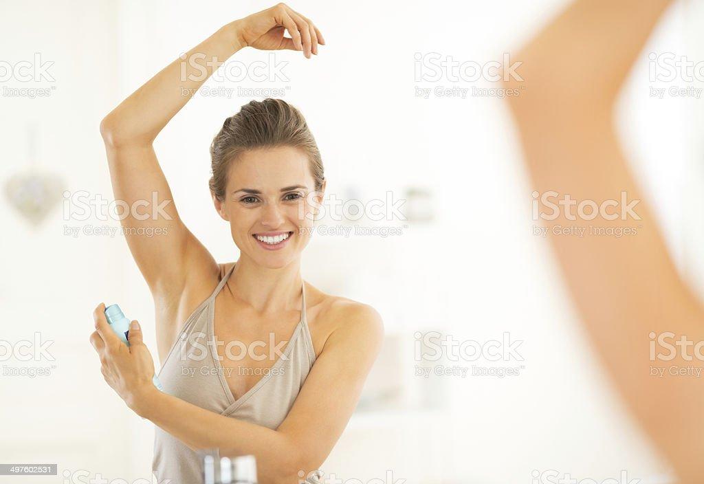 happy young woman applying deodorant on underarm stock photo