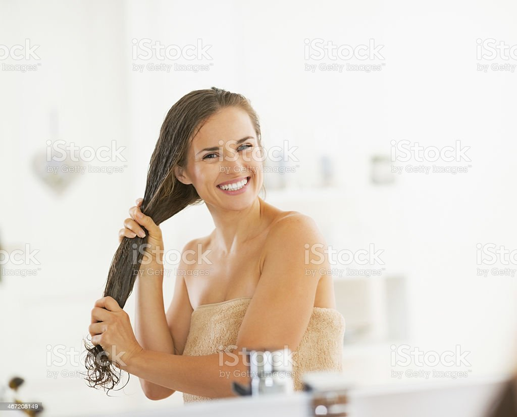 happy young woman applying hair mask in bathroom stock photo