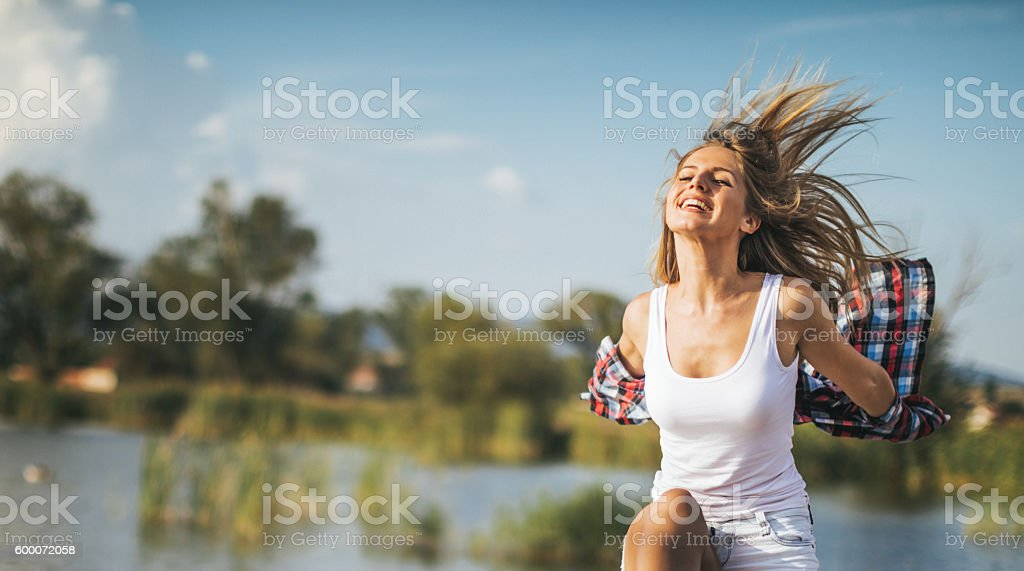 Happy young woman at lake stock photo