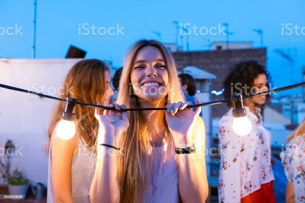 Happy young woman at the rooftop party stock photo