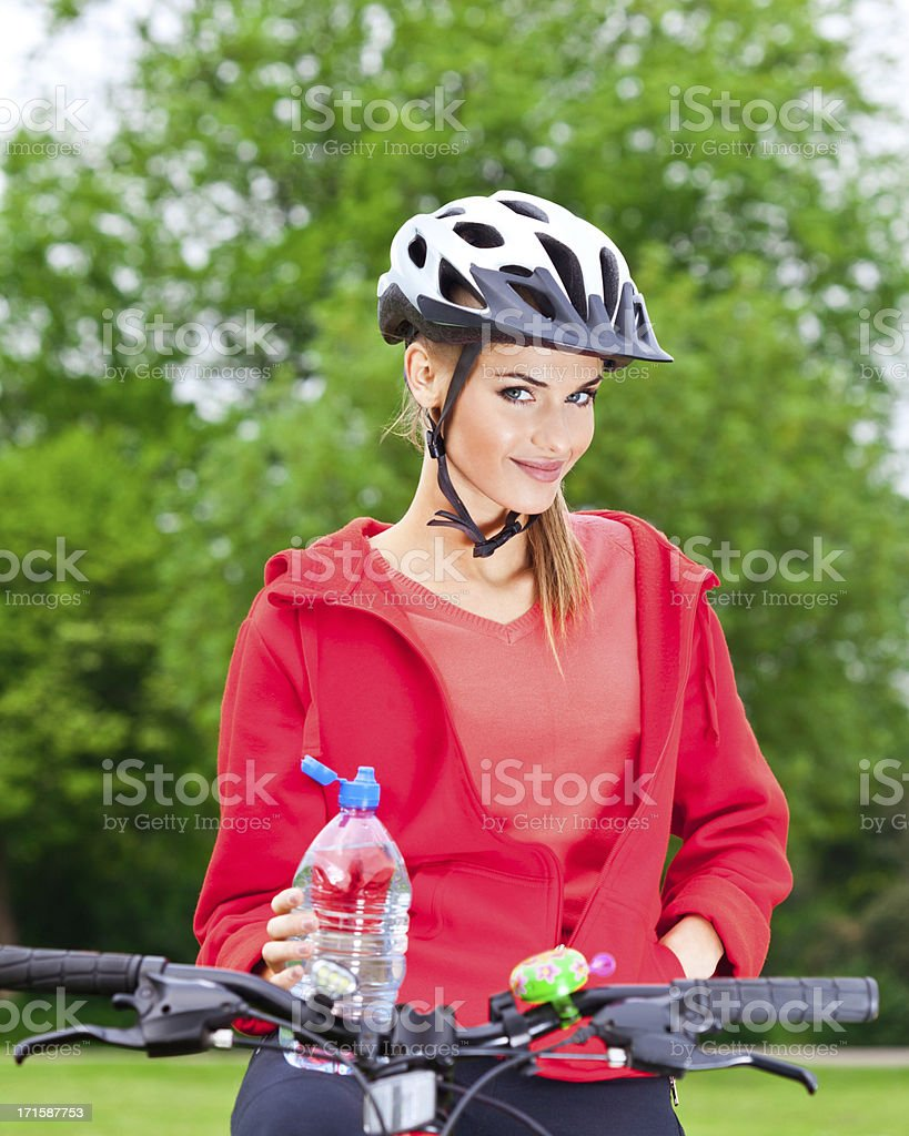 Happy young woman bicycling in a park royalty-free stock photo