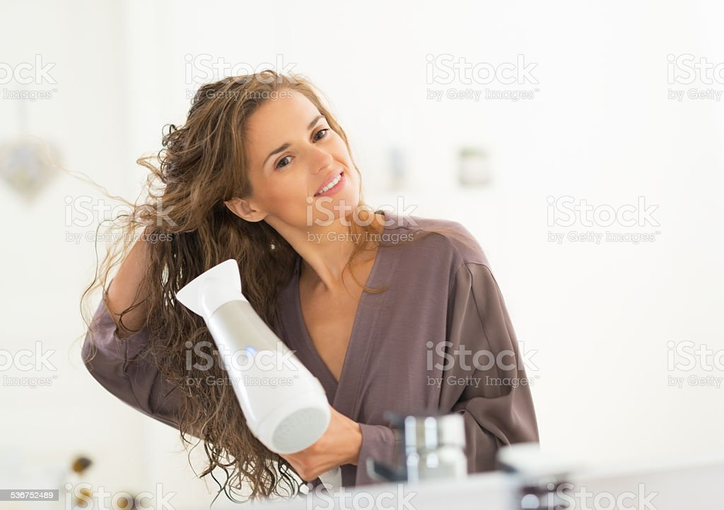 happy young woman blow drying hair in bathroom stock photo