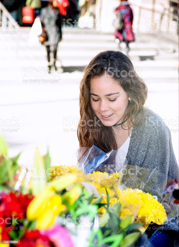 Happy young woman buying some flowers stock photo
