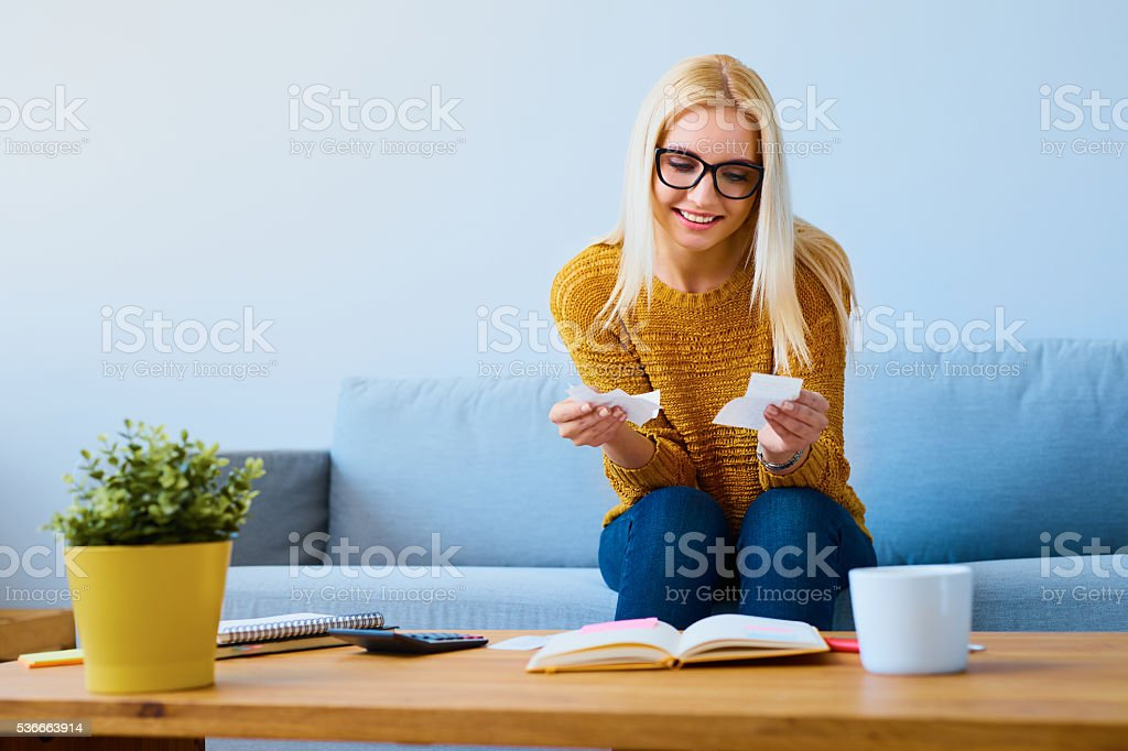 Happy young woman checking bills at home stock photo