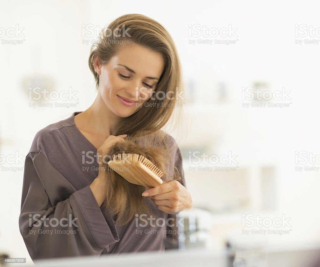 happy young woman combing hair in bathroom stock photo