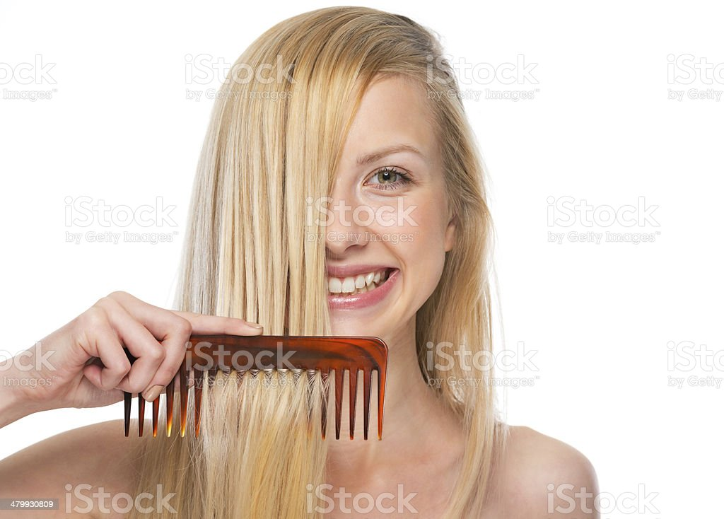happy young woman combing hair stock photo
