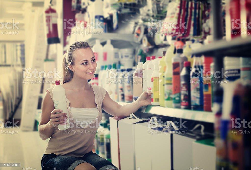 happy young woman customer choosing paint medium in bottle stock photo