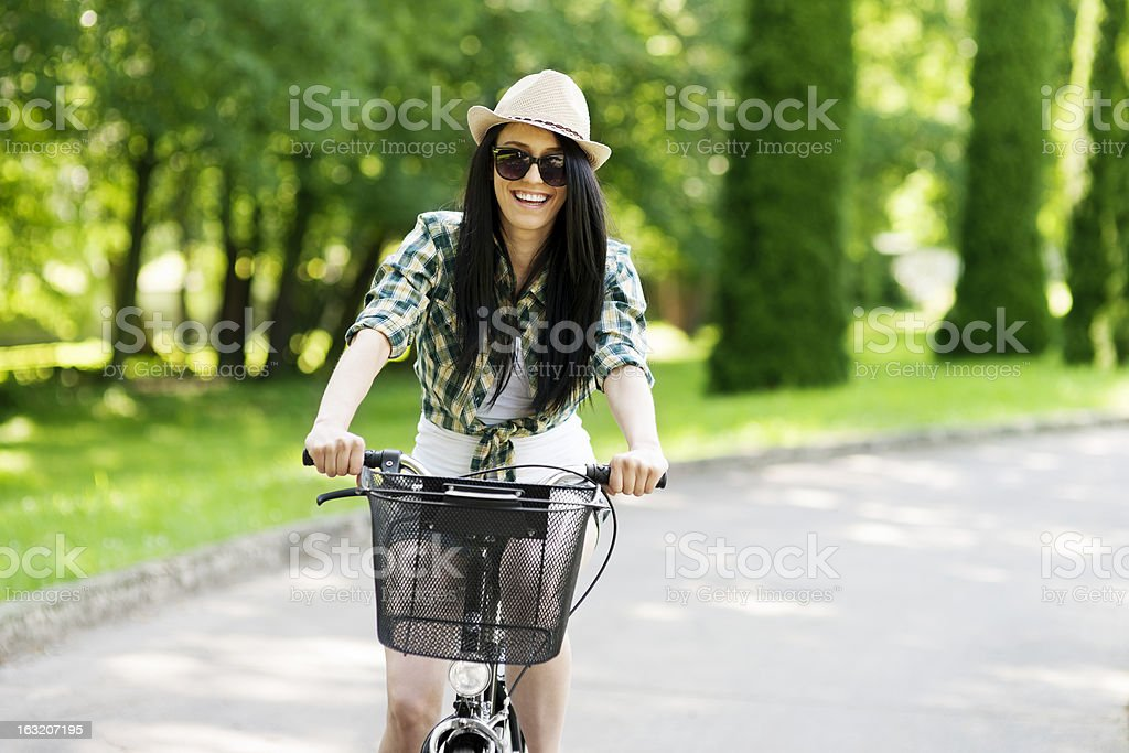 Happy young woman cycling through the park royalty-free stock photo