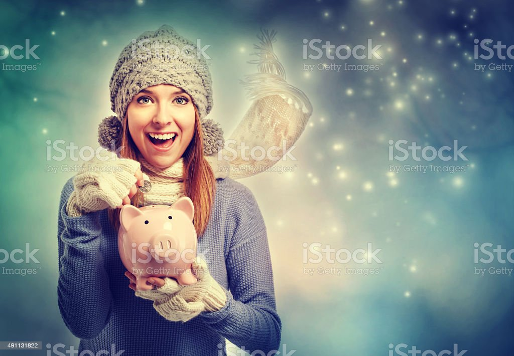 Happy young woman depositing money into her piggy bank stock photo