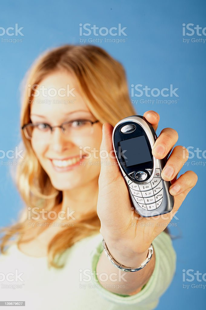 Happy young woman displaying mobile phone royalty-free stock photo