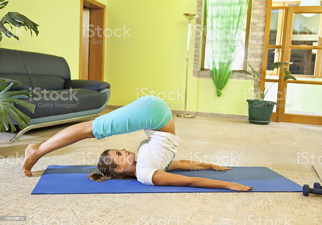 Happy young woman doing fitness at home. stock photo