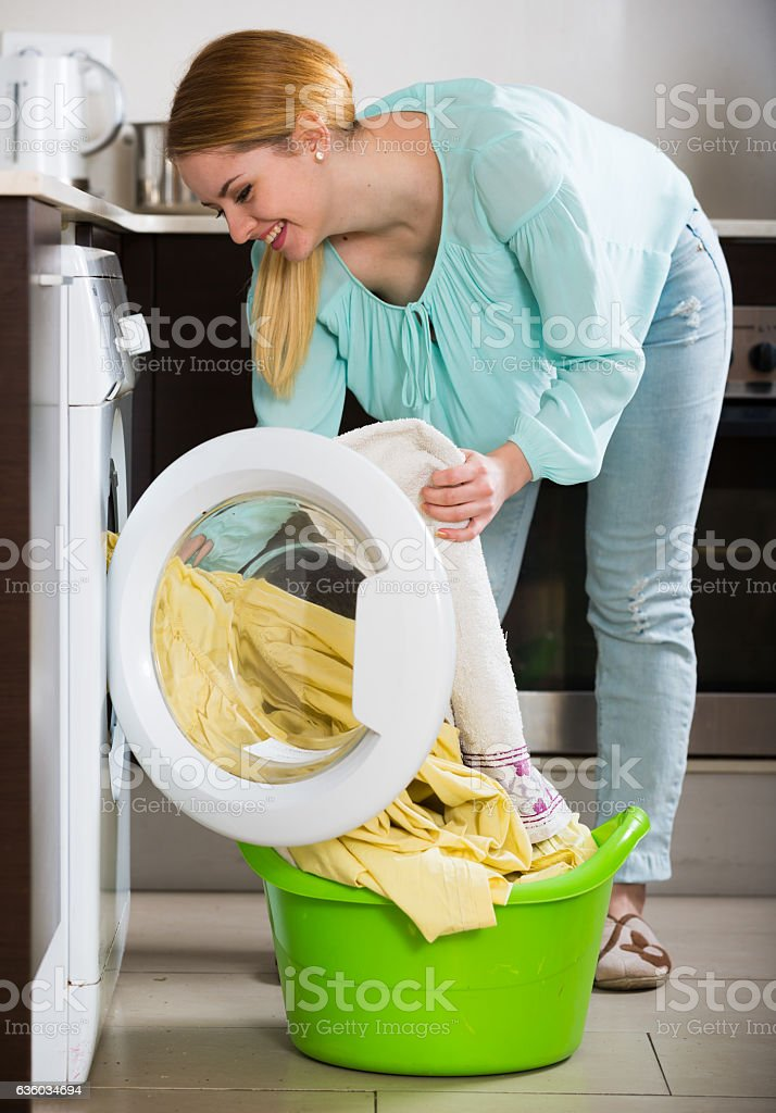 Happy young woman doing laundry in kitchen and smiling stock photo