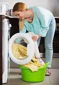 Happy young woman doing laundry in kitchen and smiling