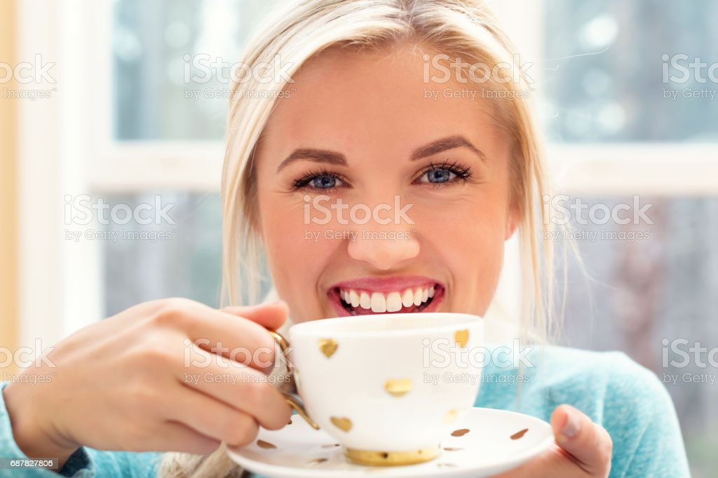 Happy young woman drinking coffee stock photo