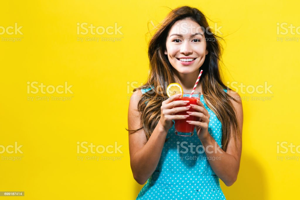 Happy young woman drinking smoothie stock photo