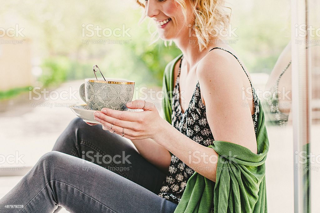 Happy young woman drinking tea stock photo