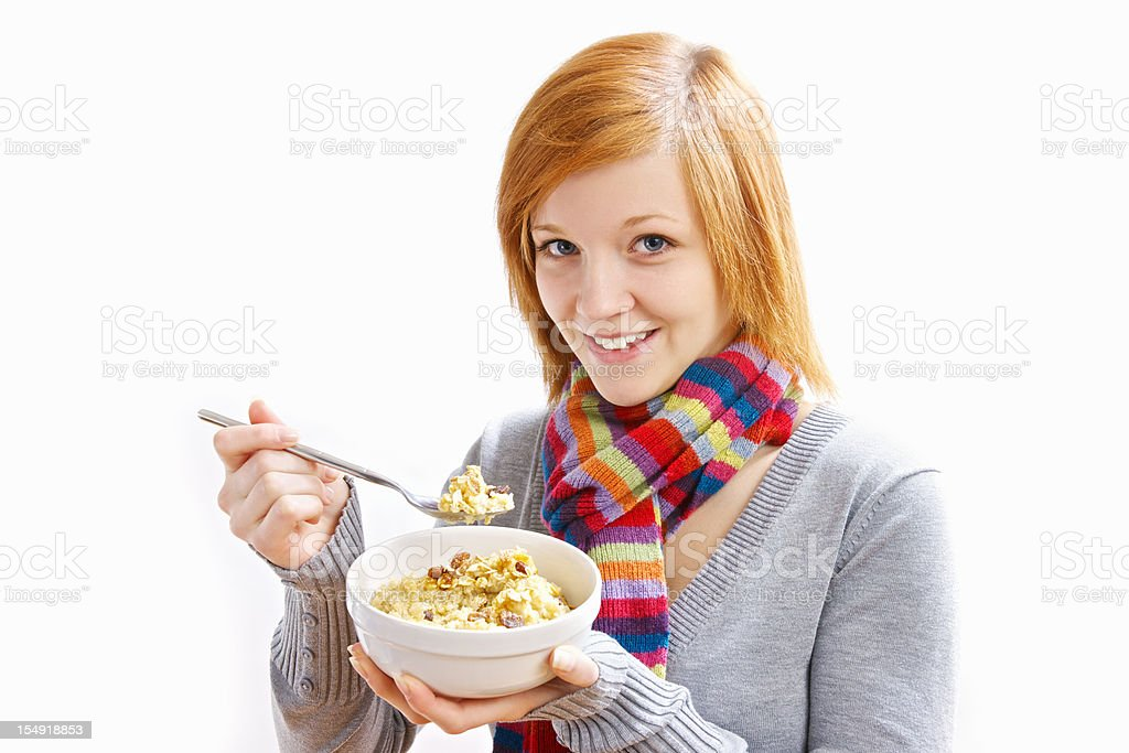Happy young woman eating a bowl of oatmeal royalty-free stock photo