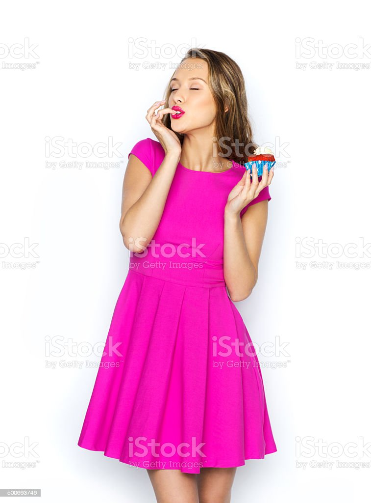 happy young woman eating birthday cupcake stock photo