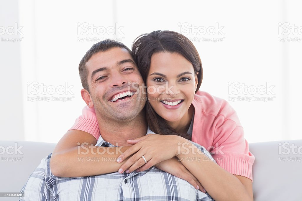 Happy young woman embracing man stock photo
