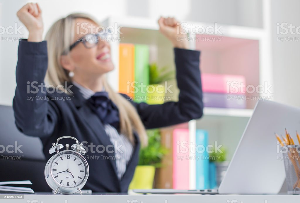 Happy young woman enjoys finishing job on time stock photo