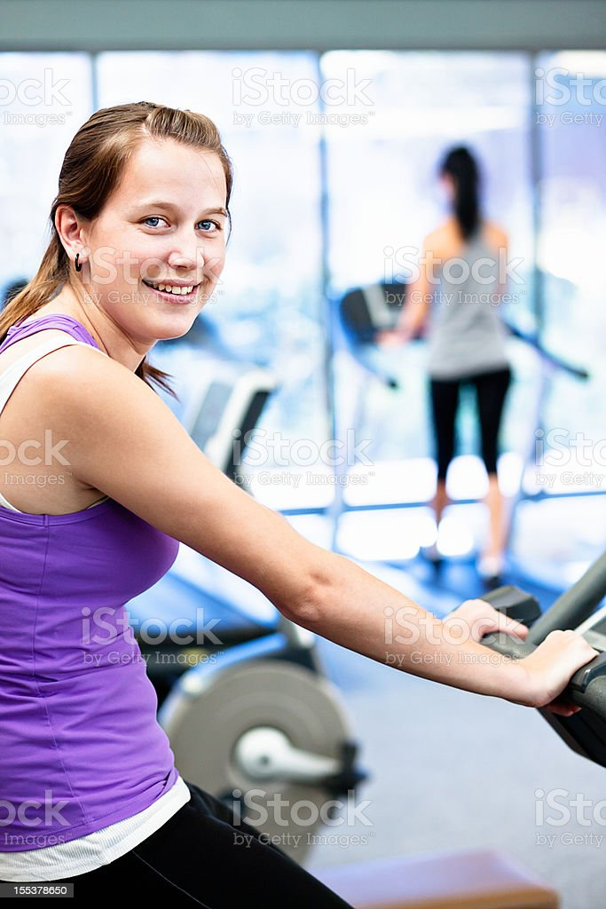 Happy young woman enjoys using exercise bike in gym stock photo