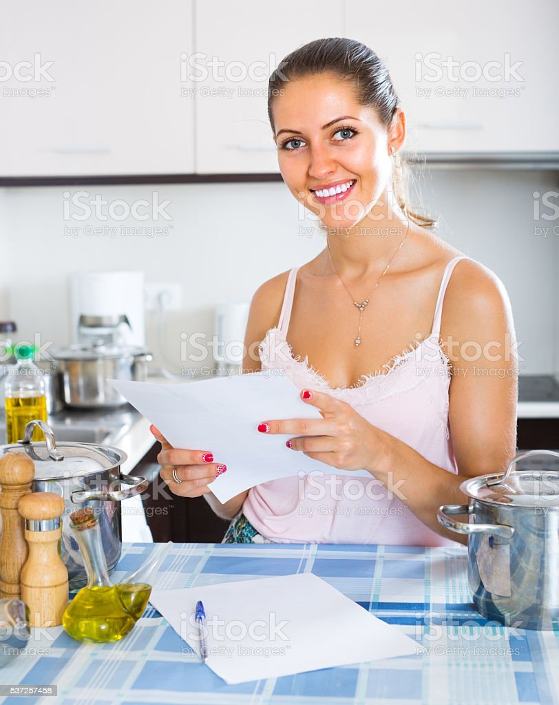 Happy young woman filling papers stock photo